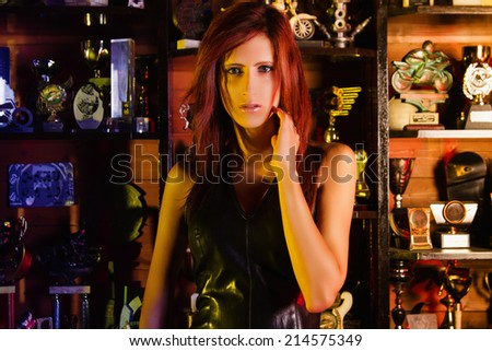 Beautiful and adult Biker girl standing in front of many trophies.