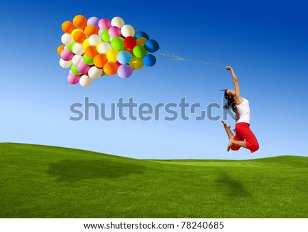 Beautiful and athletic Girl jumping with balloons on a green meadow - stock photo