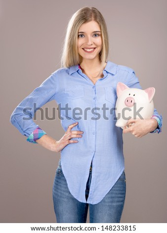 Beautiful and attractive blonde woman holding a piggy bank - stock photo