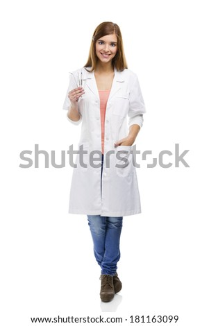 Beautiful and attractive female dentist with tools, isolated over a white background - stock photo