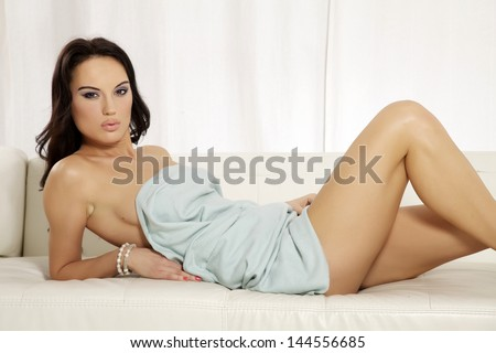 Beautiful and attractive sexy sensuality female young adult brunette woman posing in blue blanket on the white sofa