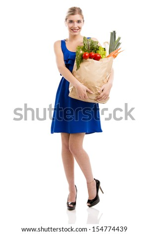 Beautiful and attractive woman carrying a bag full of vegetables, isolated over white background - stock photo