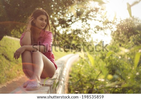 Beautiful and attractive woman sitting on a side, wearing sexy casual denim shorts with macrame, lace attachment and a pink shirt and floral shoes. Lens flare