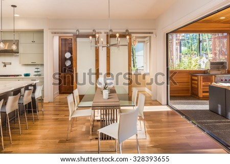 Beautiful and Bright Dining Room Interior, Kitchen, and Outdoor Patio in New Luxury Home - stock photo