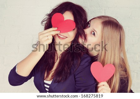 Beautiful and cheerful girlfriends are holding paper red hearts - stock photo
