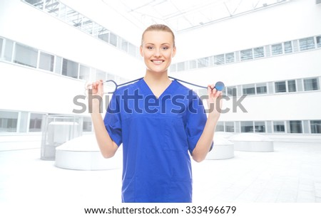 Beautiful and cheerful intern with stethoscope over hospital background. - stock photo