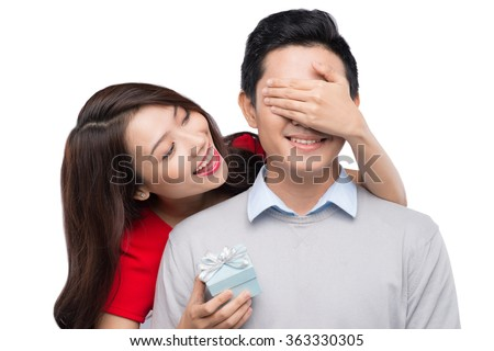 Beautiful and cheerful young asian couple in love offering gift to each other for valentine day or birthday - stock photo