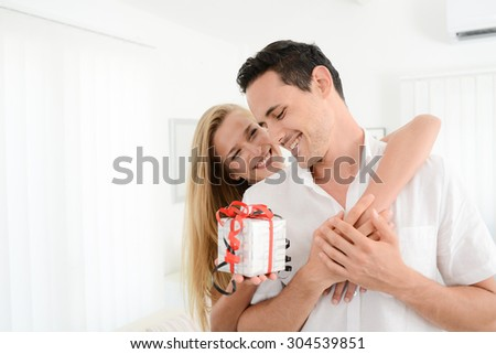 beautiful and cheerful young couple in love offering gift to each other for valentine day or birthday - stock photo
