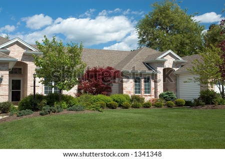 Beautiful and colorful all brick ranch style home. Gorgeous spring day with blue skies and puffy white clouds. Just one of many new house photos in my gallery. - stock photo