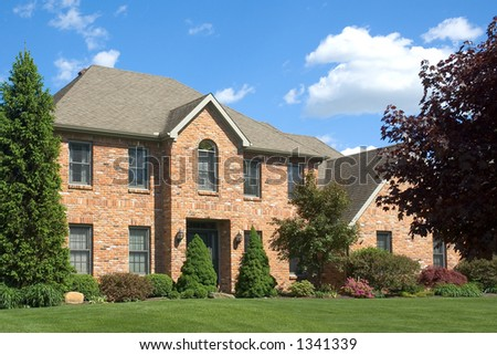 Beautiful and colorful brown two story brick home. Typical new home in the suburbs of the United States. Just one of many home or house photos in my gallery. - stock photo