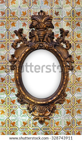 beautiful and complex brass baroque frame hanged on a tiled wall - stock photo