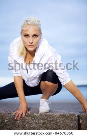 Beautiful and confident young woman doing stretching. - stock photo