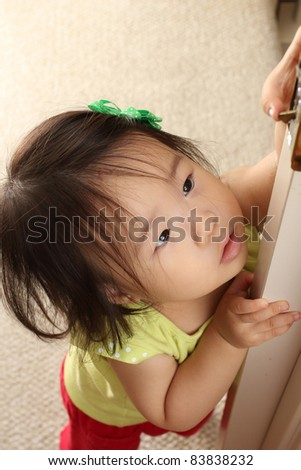 Beautiful and cute Asian 14-month old baby toddler girl playing with door latch and looking up - stock photo