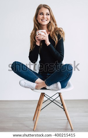 Beautiful and cute. Beautiful young woman holding coffee cup and looking away with smile while sitting on chair in lotus position against white background - stock photo