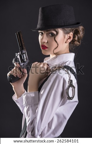 Beautiful and dangerous.Young female gangster holding the gun and holding handcuffs. isolated on dark background