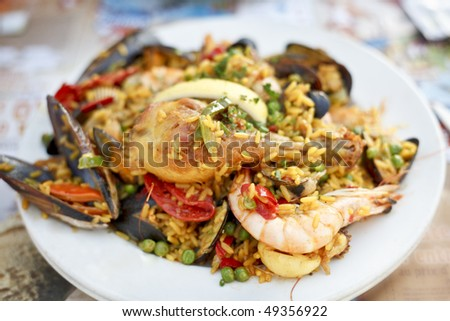 Beautiful and delicious paella in a white plate. Selective focus. - stock photo