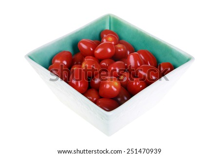 Beautiful and delicious plum cherry tomatoes in a white ceramic square bowl with a blue interior isolated on white with room for your text. Tomatoes are loved by people and animals around the world - stock photo