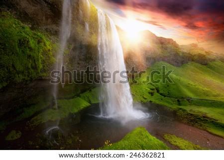 Beautiful and dramatic sunset in Seljalandsfoss waterfalls, Iceland - stock photo