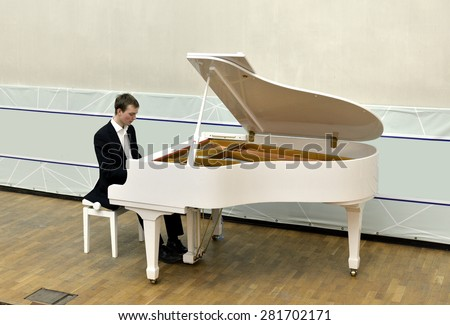 Beautiful and elegant young man plays white grand piano - stock photo