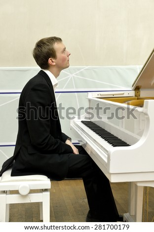 Beautiful and elegant young pianist and white grand piano - stock photo