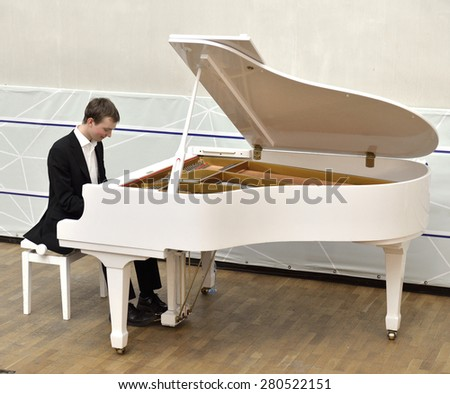Beautiful and elegant young pianist plays white grand piano - stock photo