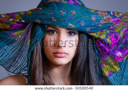 Beautiful and exotic young woman of multiple ethnicity wearing a blue/purple veil spread over her head.