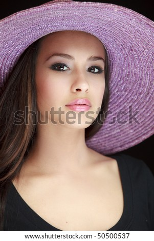 Beautiful and exotic young woman of multiple ethnicity wearing a purple hat with a black background. - stock photo