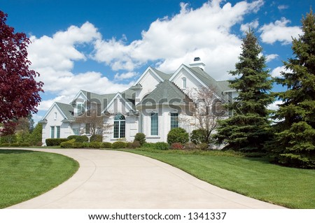 Beautiful and  expensive new home. This house features lots of roof peaks and a circular driveway. Just one of many new home or house photos in my gallery. - stock photo