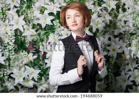 Beautiful and fashion young woman near the wall of flowers