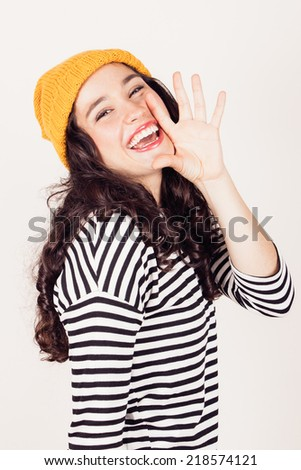 Beautiful and funny girl with striped dress and yellow wool cap shouting hand next to her mouth - stock photo