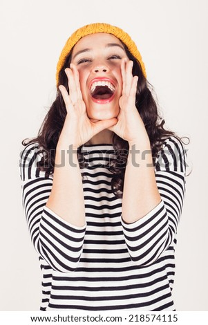 Beautiful and funny girl with striped dress and yellow wool cap shouting hands next to her mouth. Focus on mouth - stock photo