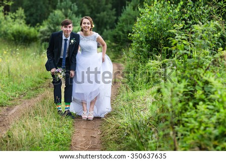 Beautiful and happy bride and groom walking in summer forest. Young wedding couple.