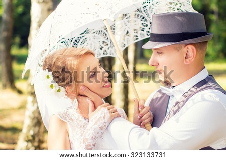 Beautiful and happy bride and groom with umbrella in a forest - stock photo