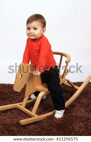 beautiful and happy child on a wood horse - stock photo