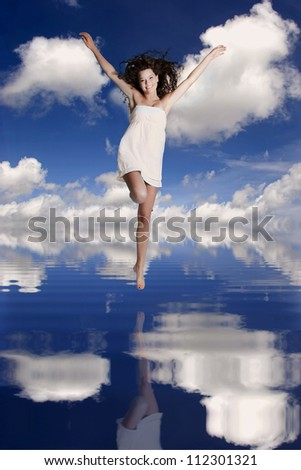 Beautiful and happy girl jumping over the water with her reflection - stock photo