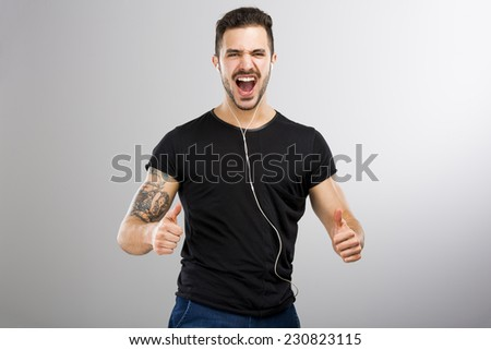 Beautiful and happy latin man listen music with thumbs up - stock photo