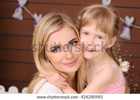 beautiful and happy mom and daughter blonde hugging - stock photo