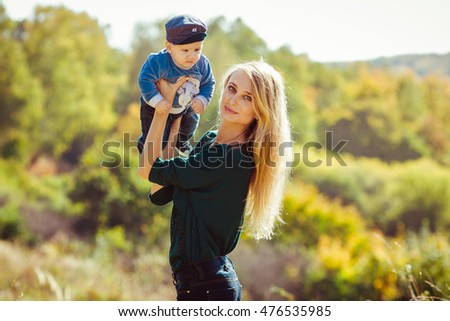Beautiful and happy mother with her little boy outdoors