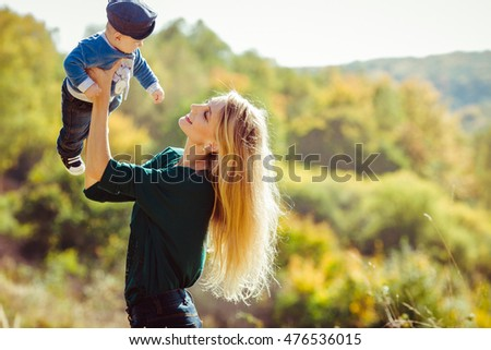 Beautiful and happy mother with her little boy playing outdoors