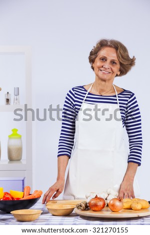 Beautiful and happy senior woman cooking at her kitchen - stock photo