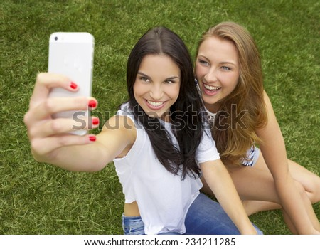 Beautiful and happy teenagers taking selfies - stock photo
