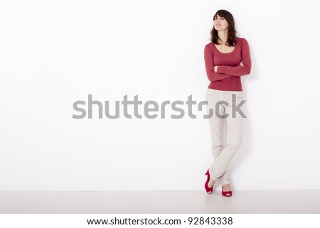 Beautiful and happy woman, against a white wall with copyspace on the left side. - stock photo