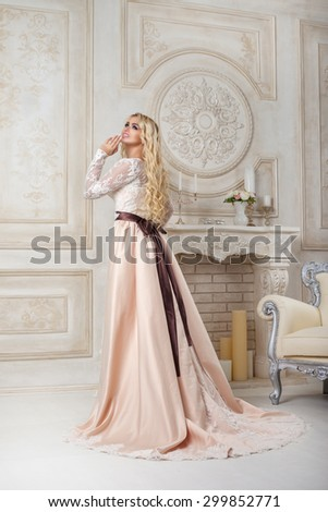 beautiful and happy woman in a wedding dress near the fireplace
