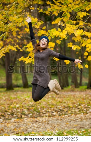 Beautiful and happy woman jumping in a autumn day - stock photo
