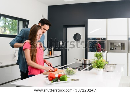 beautiful and happy young couple preparing organic vegetable salad together in kitchen at home - stock photo