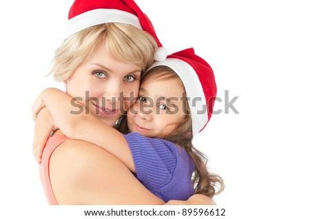 beautiful and happy young mother holding smiling daughter on her hands, Both wearing christmas santa hats and looking into the camera. Studio shot, isolated on white background.