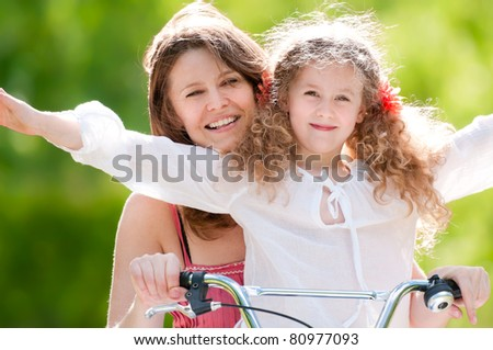 Beautiful and happy young mother on bicycle with her daughter. Both smiling, summer park in background. - stock photo