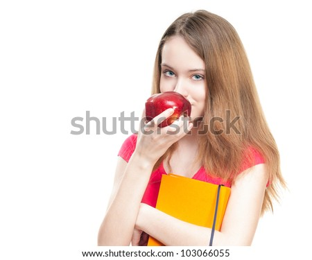 Beautiful and happy young student girl eating red apple and holding book in her hands. Looking into the camera. Isolated on white background.