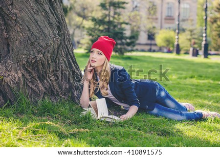 Beautiful and happy young student girl in red hat holding book lie down on green grass under the tree near the campus, university buildings, school, education, pensive. Summer or spring green park - stock photo