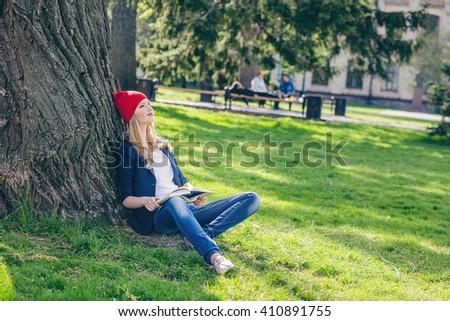 Beautiful and happy young student girl in red hat holding book sitting on green grass under the tree near the campus, university buildings, school, education. Summer or spring green park - stock photo